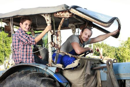 son: Father and son driving on a tractor on a farm