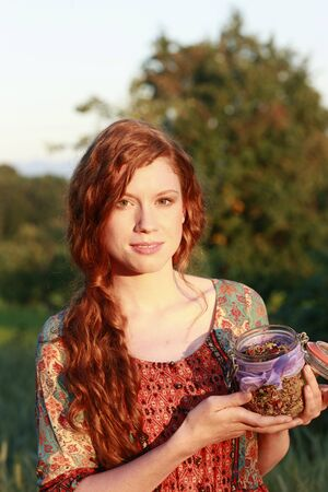 dried herbs: Attractive woman with a glass of dried herbs outdoor Stock Photo