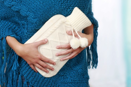 Woman with belly ache and hot bottle suffering Stockfoto