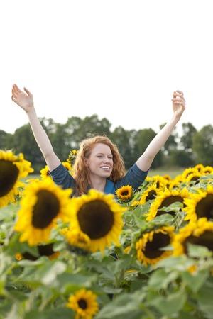 腕を上げるとひまわり畑で幸せな女 写真素材