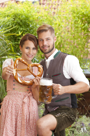 traditional costume: Bavarian couple in traditional costume with beer and brezel outdoor in a beergarden