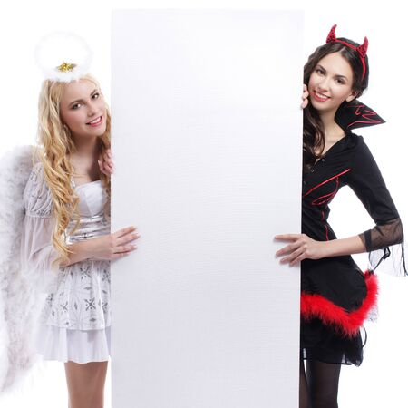 devil woman: Angel and devil woman beside a white empty wall isolated Stock Photo