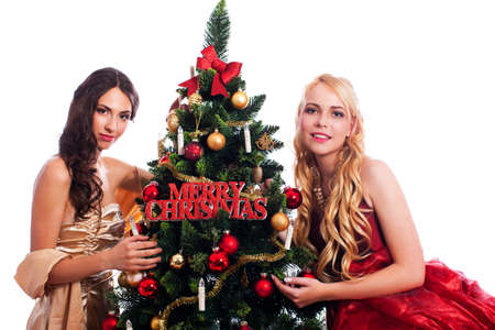 dark haired woman: Two attractive woman beside a christmas tree isolated