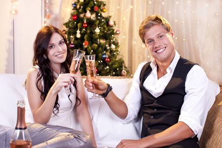 sparkling wine: Happy couple with sparkling wine on christmas or new years eve smiling