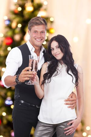 sparkling wine: Happy couple with sparkling wine glasses on christmas Stock Photo
