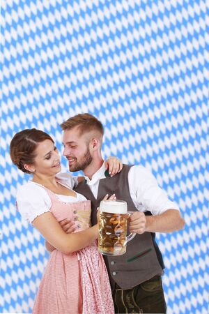 checker flag: Young couple in traditional costume in bavaria having fun Stock Photo