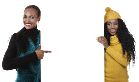 woman with camera: Two young black woman pointing at empty board Stock Photo