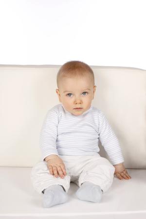 rompers: Beb� lindo que se sienta en un sof� mirando a la c�mara