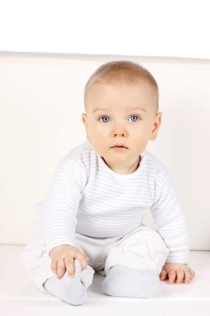 bebe sentado: Bebé lindo que se sienta en un sofá mirando a la cámara