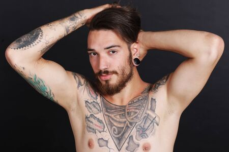 stripped: Young urban man with tattoos stripped to the waist Stock Photo