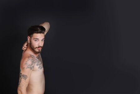 nacked: Young urban man with tattoos stripped to the waist in front of black background