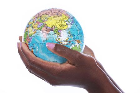 manos entrelazadas: Manos negras que sostienen un globo del mundo aislado en blanco