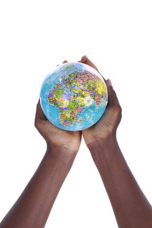 cogidos de la mano: Manos negras que sostienen un globo del mundo aislado en blanco
