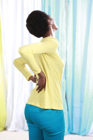 spinal disc: African woman with back pain holing her back