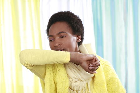 African woman with scarf coughing Stockfoto
