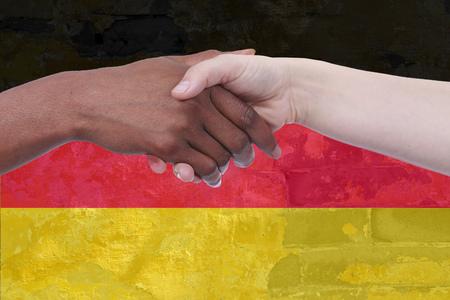 Handshake of african und european woman in front of the german flagg Reklamní fotografie