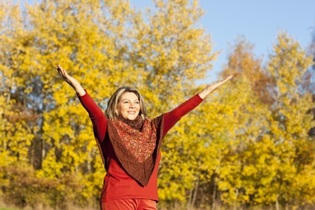Happy middle aged woman with arms outstretched in autumn