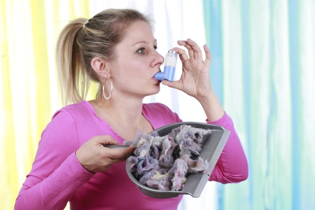 Woman with house dust allergy using asthma spray Imagens