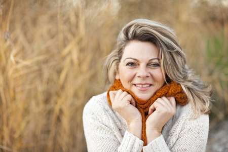 menopause: Happy middle aged woman with pullover and scarf outdoor Stock Photo