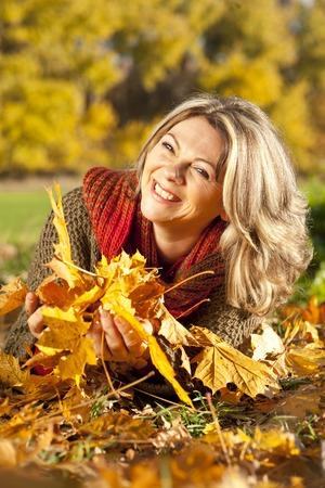 Bonne femme d'âge moyen se situant dans les feuilles d'automne Banque d'images - 47722083
