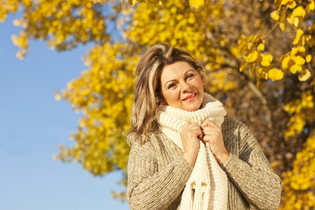 Happy middle aged woman with scarf in fall