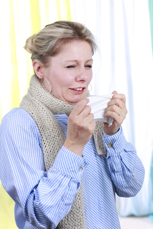 shiver: Woman with handkerchief  is blowing her nose in the office freezing