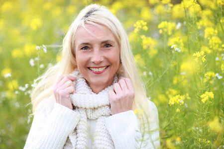 matured: Happy matured woman with scarf smiling in beautiful flowerfield