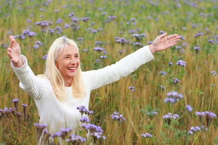 Happy matured woman smiling with rised arms in flower field Reklamní fotografie