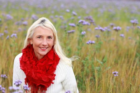 Happy matured woman with scarf smiling in beautiful flowerfield