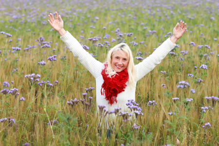 matured: Happy matured woman smiling with rised arms in flower field Stock Photo