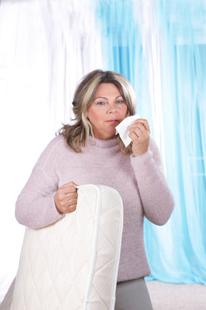 matured: Matured woman with matrace and handkerchief suffering from allergy Stock Photo