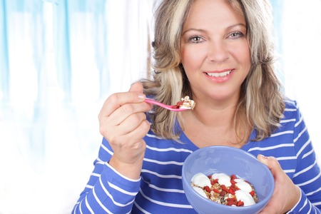 Happy matured woman eating healthy food 스톡 콘텐츠