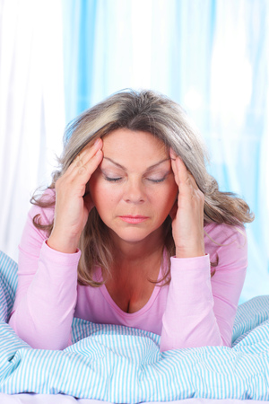 Matured woman in bed with strong headache and migraine Stockfoto