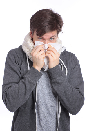 hankie: Young man blowing his nose with a handkerchief