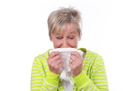 Older woman with handkerchief sneezing