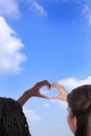 european integration: Black and white hand forming a heart in front of a blue sky