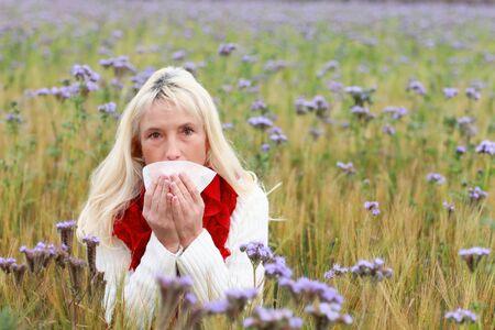 Midden oude vrouw met zakdoek in een bloem veld die lijden aan allergie Stockfoto