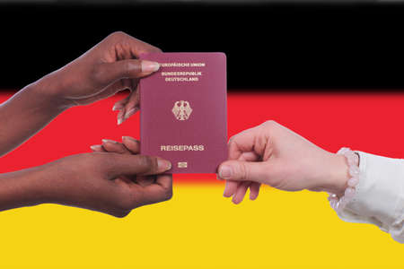 german flag: Black and white hands holding a german passport in front of the german flag