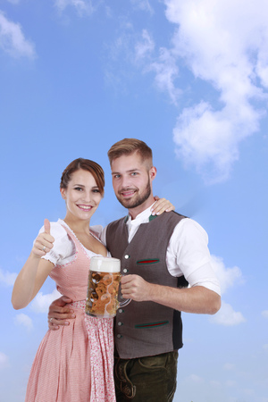 prost: Happy young couple with beer and traditional costume in front of blue sky