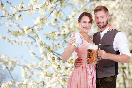 Happy young couple with beer and traditional costume in front of a flowering tree