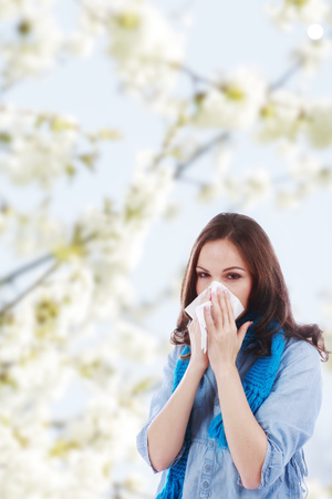 hankie: Woman with handkerchief and hay fever in front of a flowering tree Stock Photo