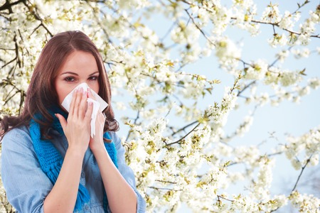 Woman with handkerchief and hay fever in front of a flowering tree Stockfoto