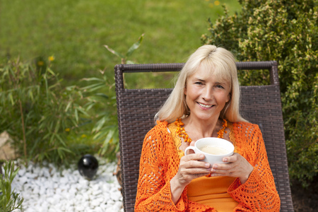 midlife: Happy middleage woman relaxing with coffee in a deck chair in her garden