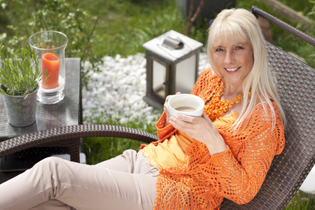 Happy middleage woman relaxing with coffee in a deck chair in her garden