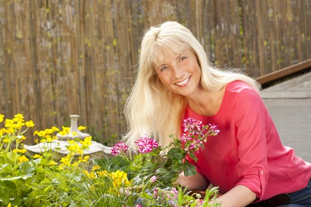 midlife: Happy middle age woman with flowers and plants in her garden in summer Stock Photo