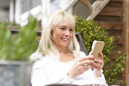 midlife: Happy middle age woman with mobile phone in the garden Stock Photo