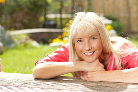 midlife: Happy middle aged woman leaning over wooden Terrace in the garden