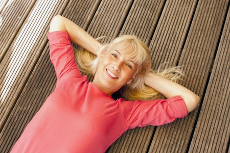 Happy middle age woman lying on wooden planks smiling Reklamní fotografie