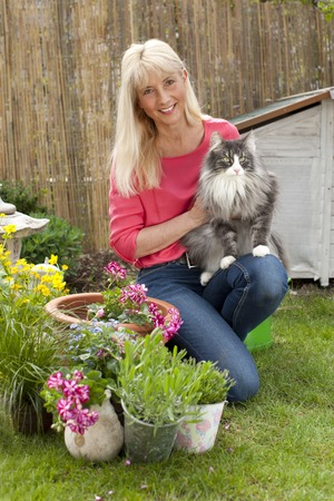 midlife: Happy middle aged woman with her cat in her garden in summer Stock Photo