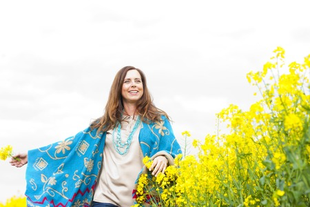 stretched: Happy middle scent woman in flower field with arms stretched Stock Photo